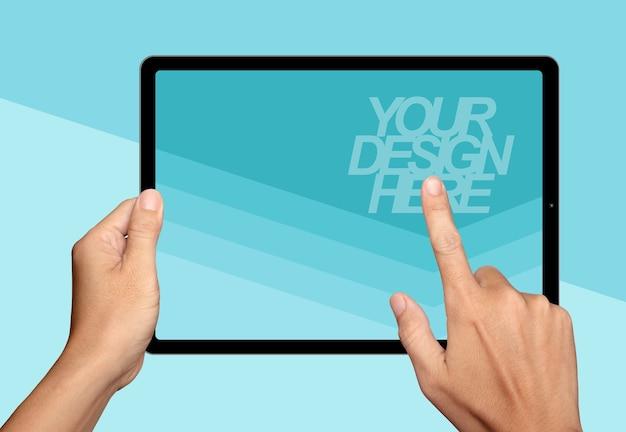 Mãos segurando e aponte na maquete do tablet
