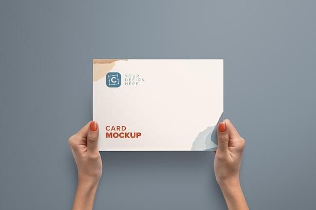 Mãos segurando um modelo de cartão de papel de paisagem Psd Premium