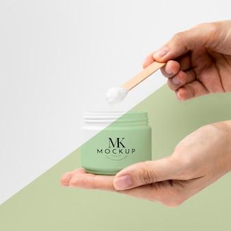 Mãos segurando um modelo de produto de beleza