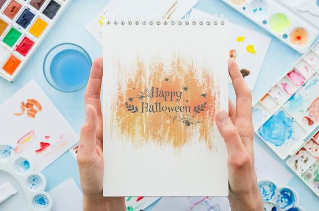 Mãos segurando um notebook com mensagem de halloween