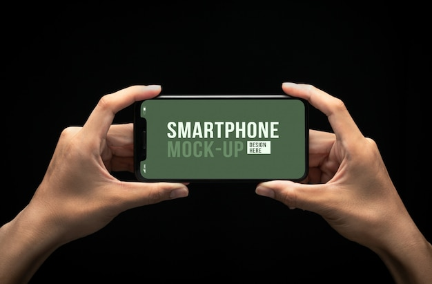 Mãos segurando um smartphone moderno com modelo de maquete de tela