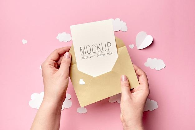 Mãos segurando uma maquete de cartão com nuvens de papel e corações
