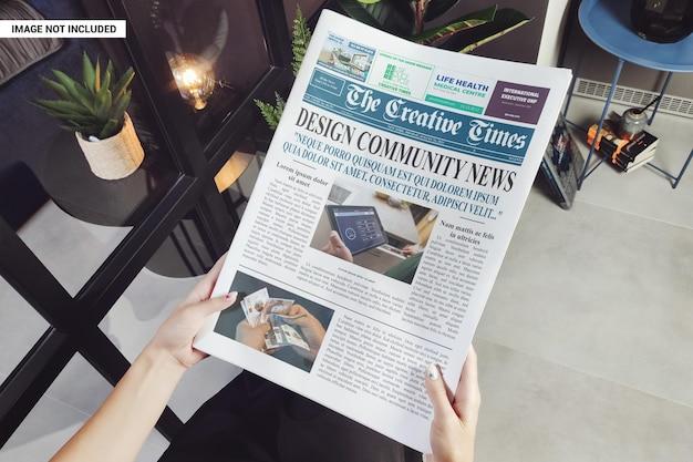 Mãos segurando uma maquete de jornal de negócios