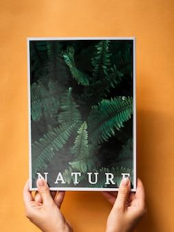 Mãos segurando uma revista de natureza em um fundo laranja