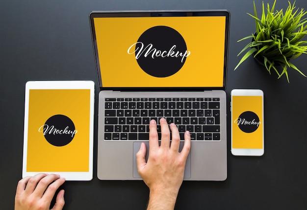 Mãos tocando maquete de dispositivos de web design responsivo