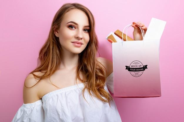 Maquete branco pacote nas mãos de uma menina em um espaço rosa