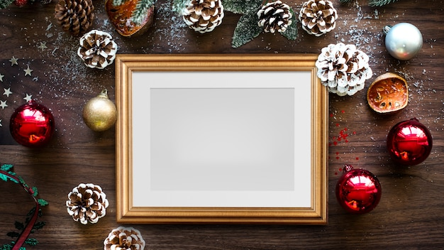 Maquete clássica de moldura dourada com decorações de natal em fundo de madeira
