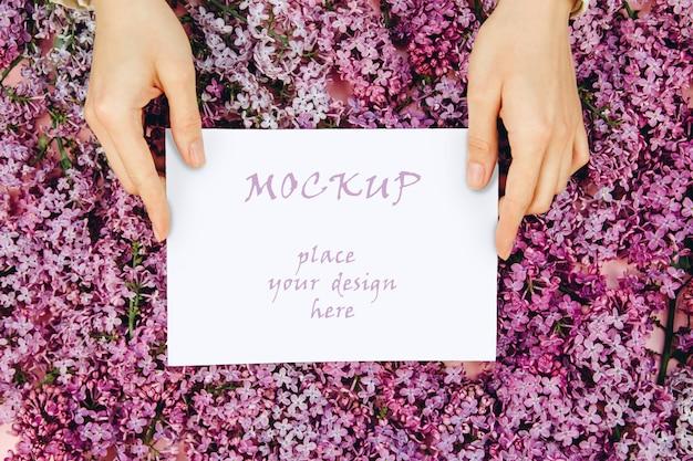 Maquete com um cartão postal nas mãos das mulheres em um fundo rosa com ramos de flores lilás