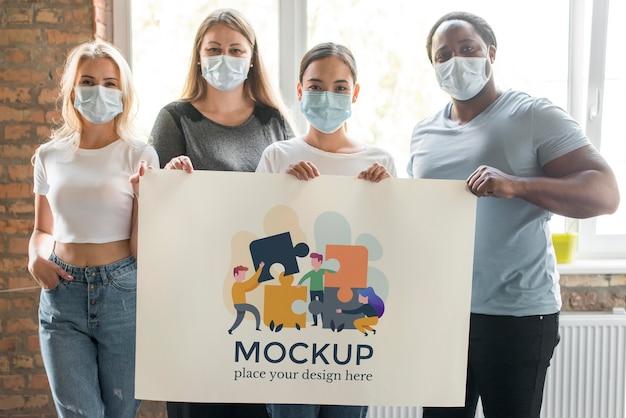 Maquete da comunidade com um grupo de pessoas segurando a maquete do banner