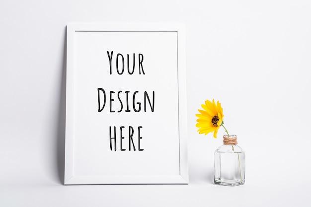 Maquete da moldura branca e vazia com flor amarela em frasco de vidro
