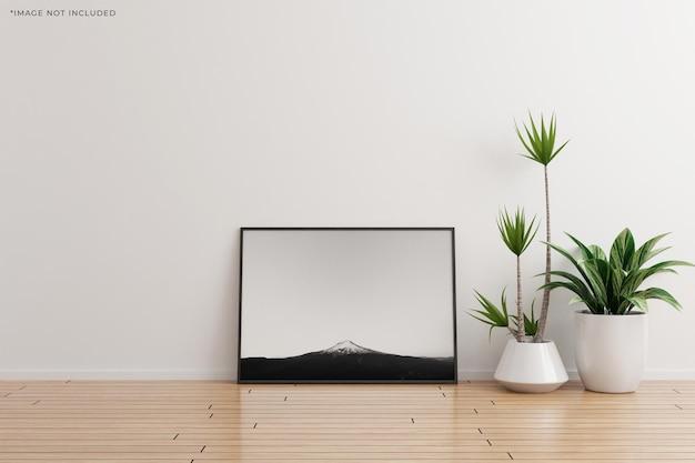 Maquete da moldura da foto horizontal preta na parede branca do quarto vazio com plantas no chão de madeira