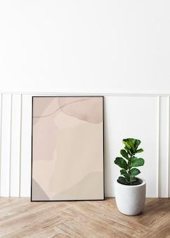 Maquete da moldura de uma foto de uma figueira com folhas de violino em um piso de parquete