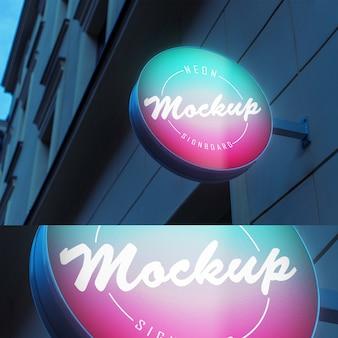 Maquete da tabuleta de néon brilhante luminescente luz com forma de círculo na construção de parede à noite