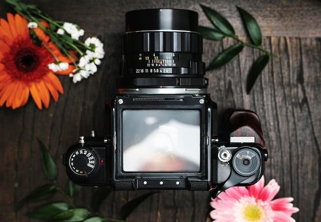 Maquete da tela da câmera analógica cercada por flores