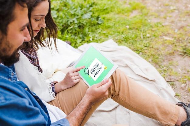 Maquete de acampamento de verão com casal usando tablet