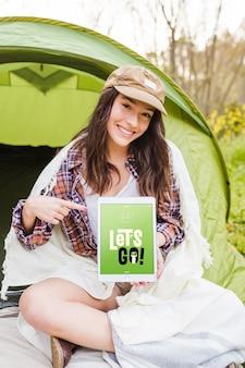 Maquete de acampamento de verão com mulher apontando para tablet