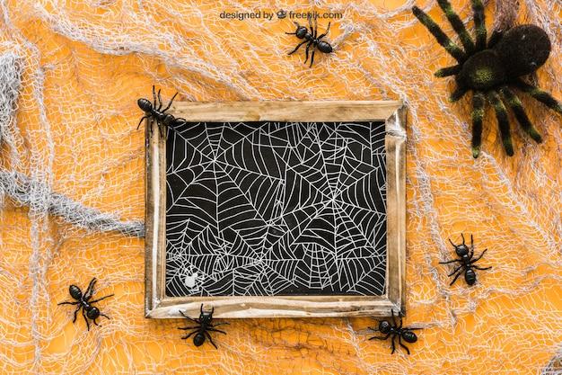 Maquete de ardósia de halloween com formigas e aranha
