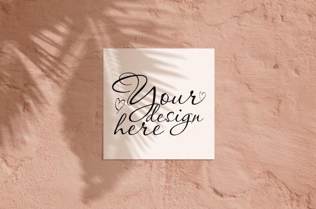 Maquete de artigos de papelaria moderna luz solar de verão. flat lay top view cartão em branco com folha de palmeira e sobreposição de sombra de ramos