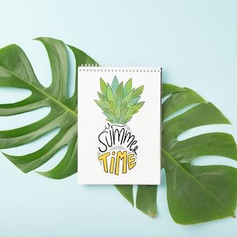 Maquete de bloco de notas em espiral na folha de palmeira