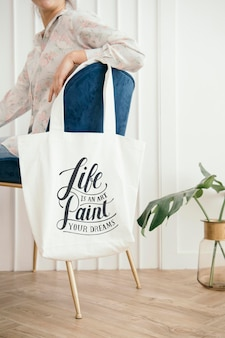 Maquete de bolsa branca pendurada em uma cadeira de veludo azul
