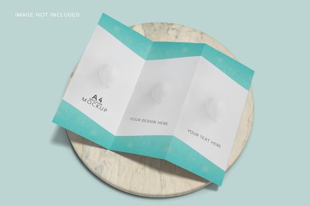 Maquete de brochura com três dobras em close-up na superfície de cerâmica