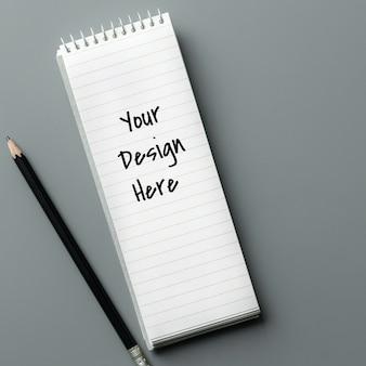 Maquete de caderno e um lápis