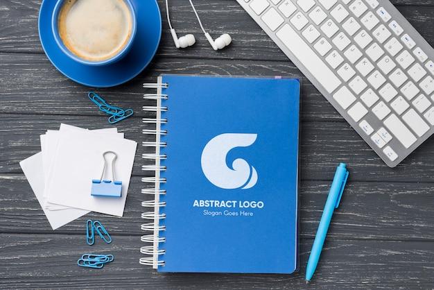 Maquete de caderno plana leigos e artigos de papelaria perto de café e teclado