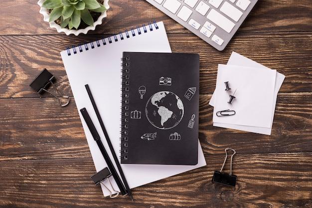 Maquete de caderno plana leigos e artigos de papelaria perto de planta e teclado suculentos