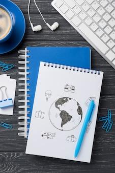 Maquete de caderno plana leigos e artigos de papelaria perto de teclado e café
