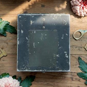 Maquete de caixa azul de metal grunge em uma mesa de madeira