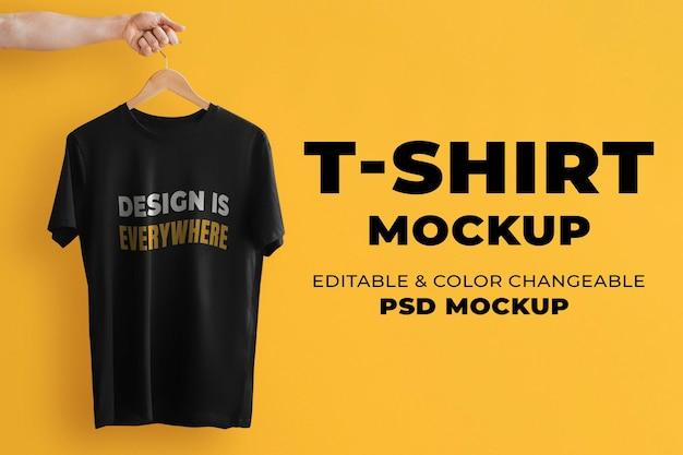 Maquete de camiseta simples psd em preto com uma mão segurando um cabide