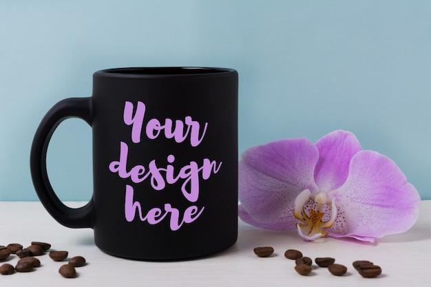 Maquete de caneca preta com orquídea e grãos de café