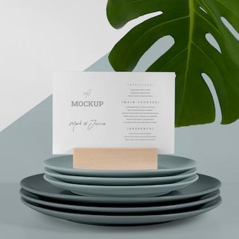 Maquete de cardápio com folha de monstera e pratos