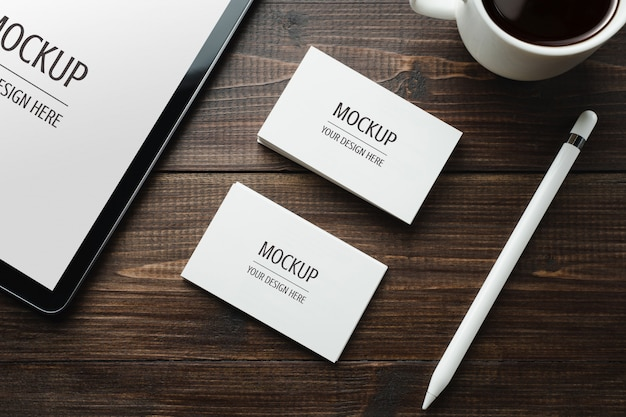 Maquete de cartão branco em branco e tablet com caneta