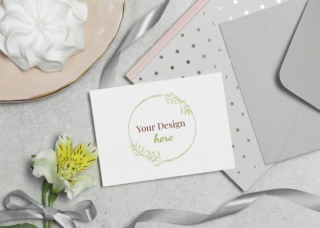 Maquete de cartão com flor, marshmallow e fita em fundo cinza