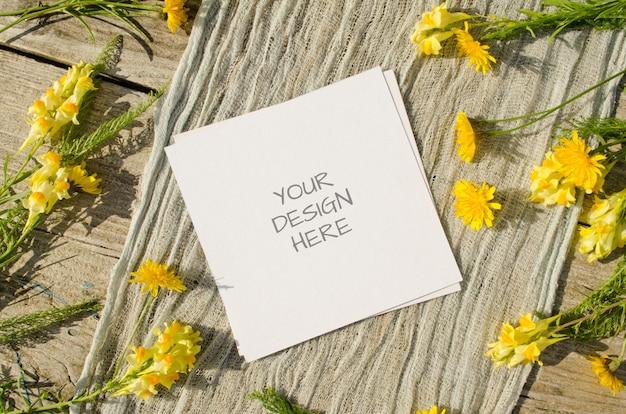 Maquete de cartão com flores amarelas em fundo de madeira velha em estilo rústico