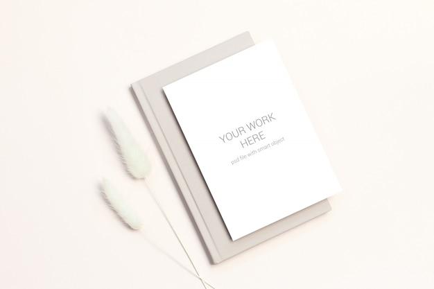 Maquete de cartão com flores secas no livro