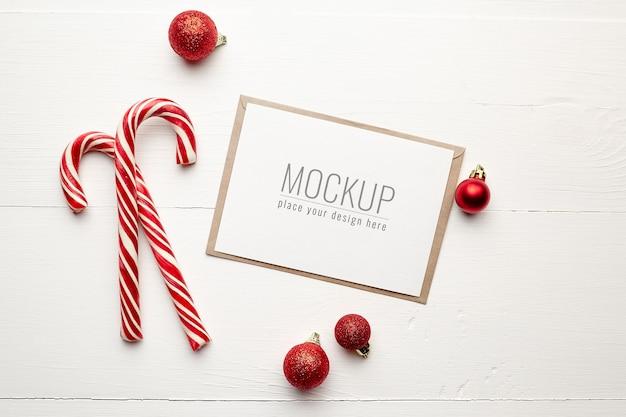 Maquete de cartão comemorativo com bastões de doces e enfeites de natal