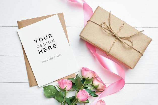 Maquete de cartão comemorativo com caixa de presente e flores rosas