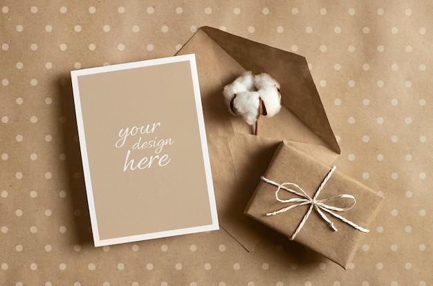 Maquete de cartão comemorativo com caixa de presente, envelope e flor de algodão