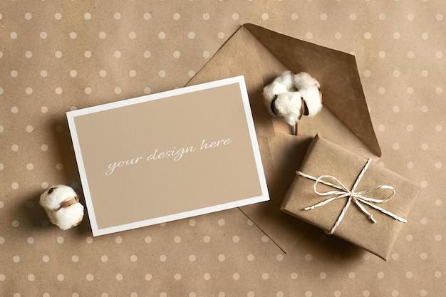 Maquete de cartão comemorativo com caixa de presente, envelope e flores de algodão