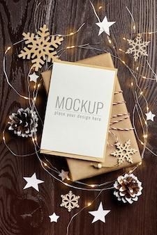Maquete de cartão comemorativo com caixa de presente, pinhas, enfeites de madeira e guirlanda de natal