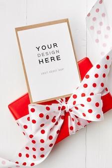 Maquete de cartão comemorativo com caixa de presente vermelha com laço