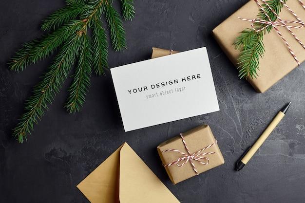 Maquete de cartão comemorativo com caixas de presente de natal e galhos de árvores de abeto no escuro