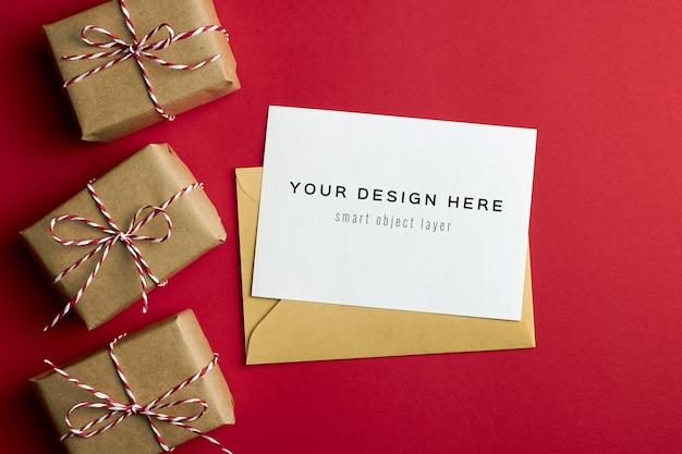 Maquete de cartão comemorativo com caixas de presente de natal em fundo de papel vermelho