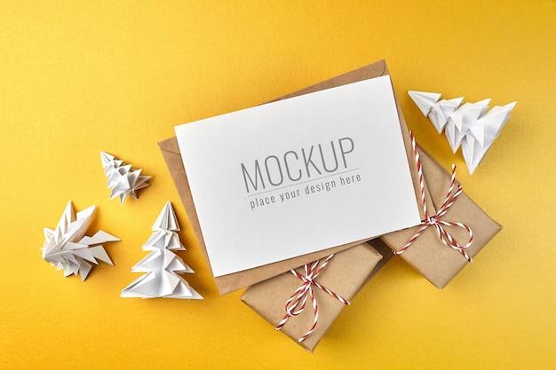 Maquete de cartão comemorativo com caixas de presente e árvores de natal de papel