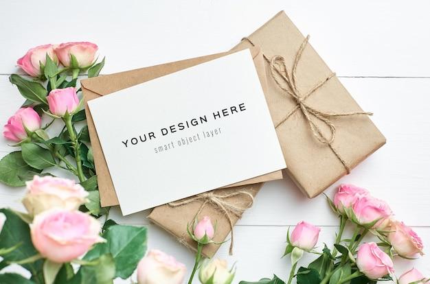 Maquete de cartão comemorativo com caixas de presente e flores rosas