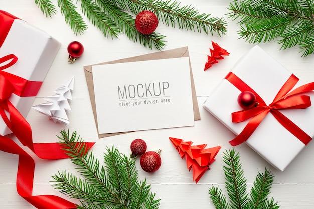 Maquete de cartão comemorativo com decorações de natal e galhos de pinheiros