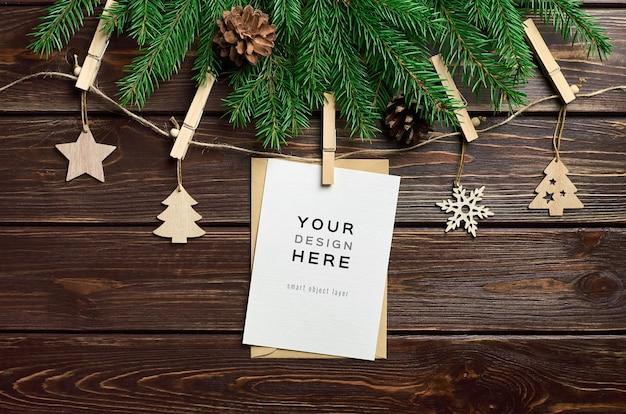 Maquete de cartão comemorativo com decorações de natal em madeira e galhos de pinheiros