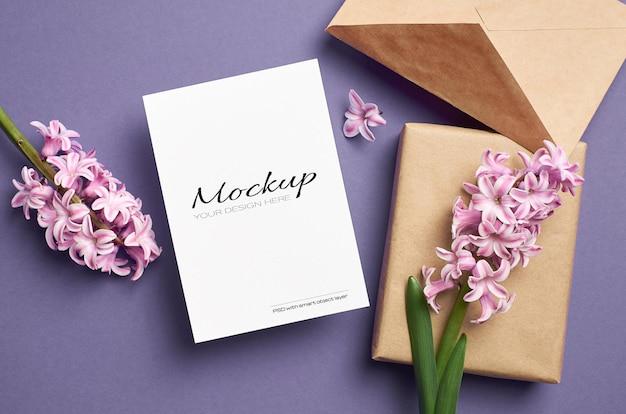 Maquete de cartão comemorativo com envelope, caixa de presente e flores de jacinto rosa